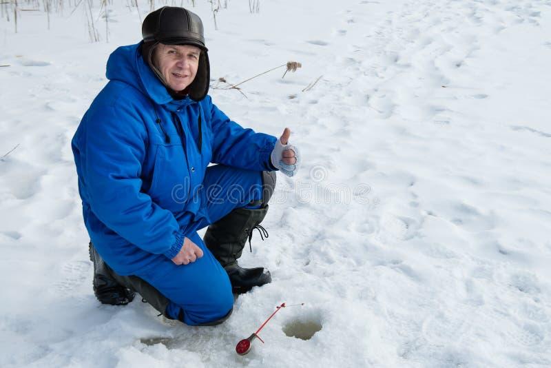 Mani dell'uomo anziano su durante la pesca sul lago al giorno di inverno freddo fotografia stock