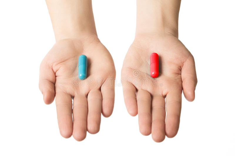 Mani dell'uomo che danno due grandi pillole Azzurro e colore rosso Faccia la vostra selezione Salute o ill Scelga il vostro lato immagini stock