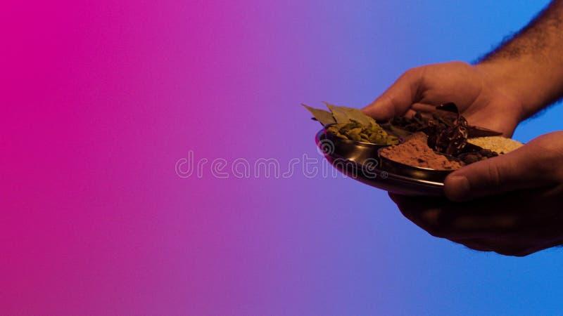 Mani dell'uomo che danno un piatto dell'insieme della spezia alle mani indiane della donna, isolato su fondo blu e rosa azione Ch immagini stock libere da diritti
