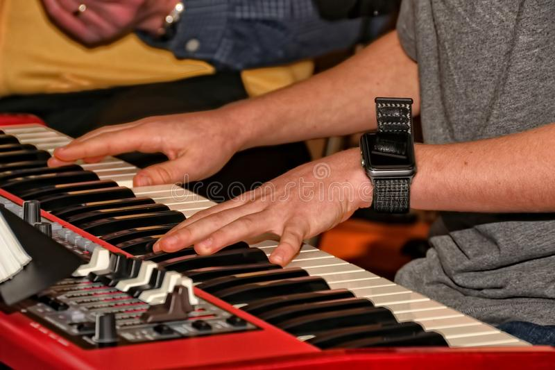 Mani dell'uomo che giocano una tastiera elettronica fotografie stock