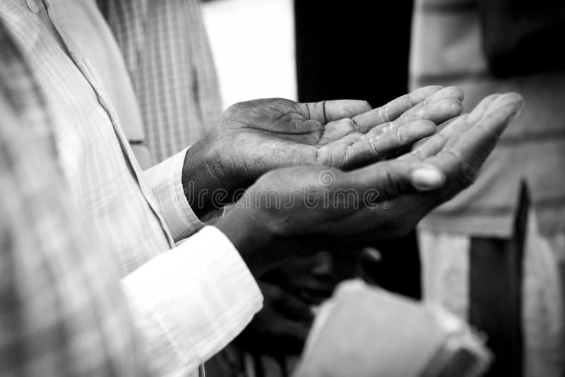 Mani dell'uomo che pregano nel Sudan del sud immagini stock libere da diritti