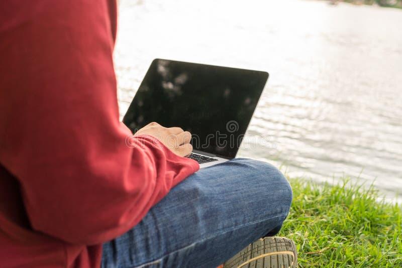 Mani dell'uomo che scrivono sul computer portatile accanto al lago fotografie stock