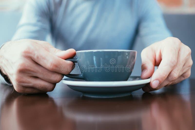 Mani dell'uomo che tengono il latte del cappuccino del tè del caffè della tazza fotografie stock
