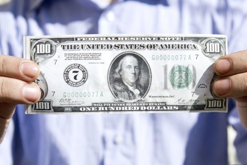 Mani dell'uomo che tengono U S Cento dollari fotografia stock libera da diritti