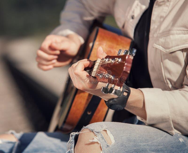 Mani dell'uomo con la fine della chitarra sull'immagine immagini stock
