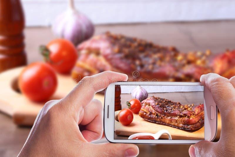 Mani dell'uomo con lo smartphone che prende a foto la bistecca arrostita di Striploin del barbecue delle costole di carne di maia fotografia stock