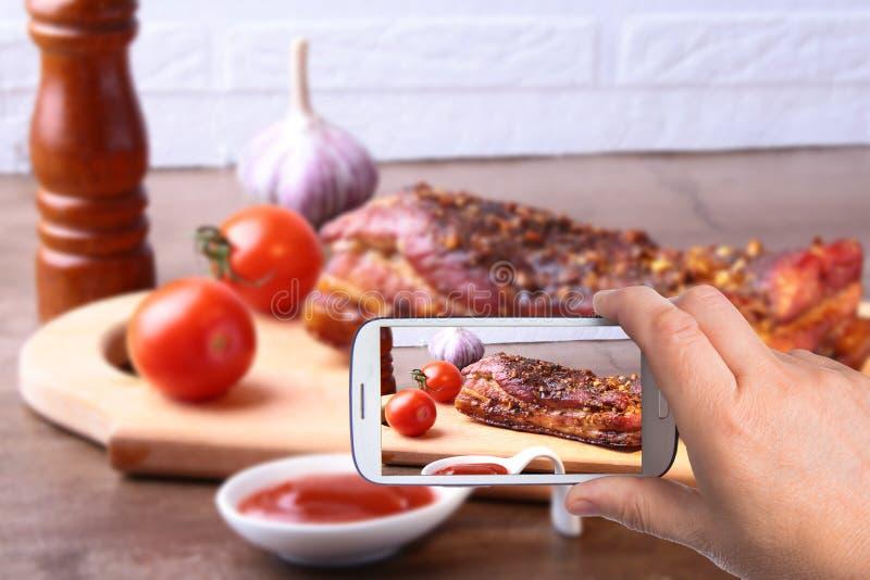 Mani dell'uomo con lo smartphone che prende a foto la bistecca arrostita di Striploin del barbecue delle costole di carne di maia immagini stock