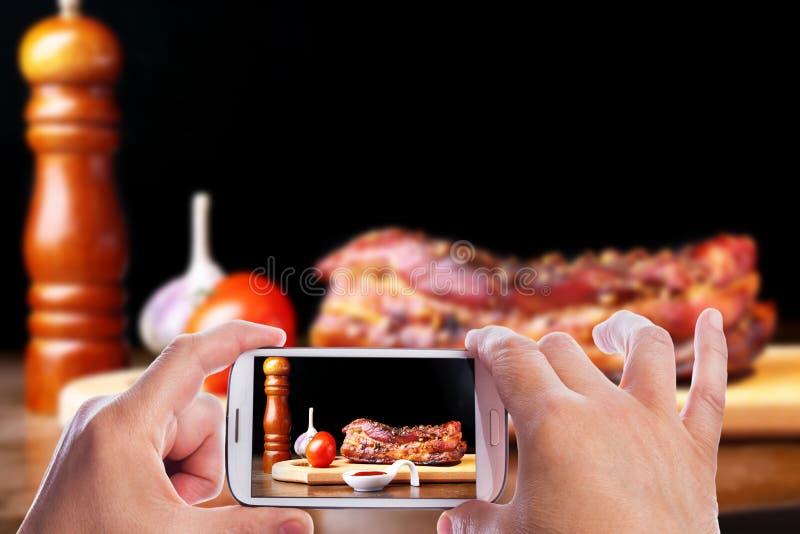 Mani dell'uomo con lo smartphone che prende a foto la bistecca arrostita di Striploin del barbecue delle costole di carne di maia fotografia stock libera da diritti
