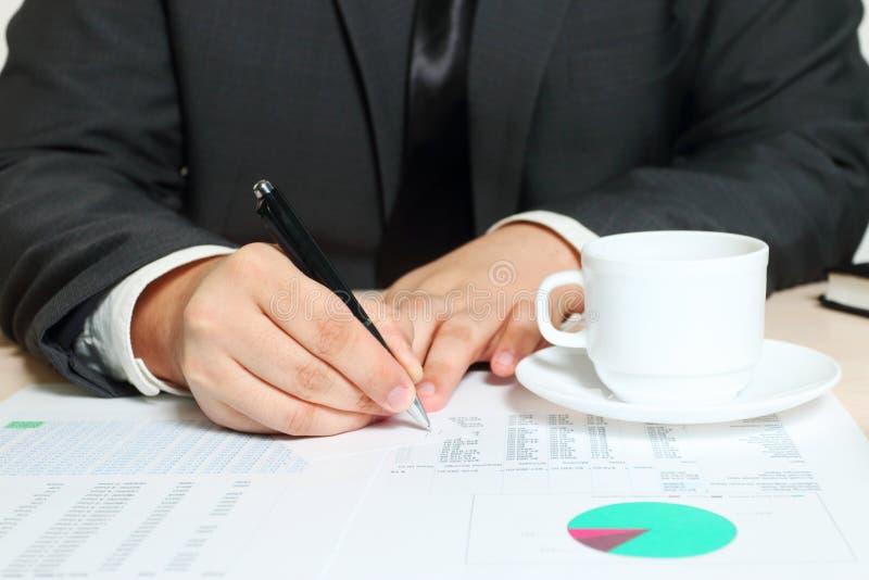 Mani dell'uomo d'affari di scrittura che si siedono alla tavola con la tazza fotografia stock libera da diritti
