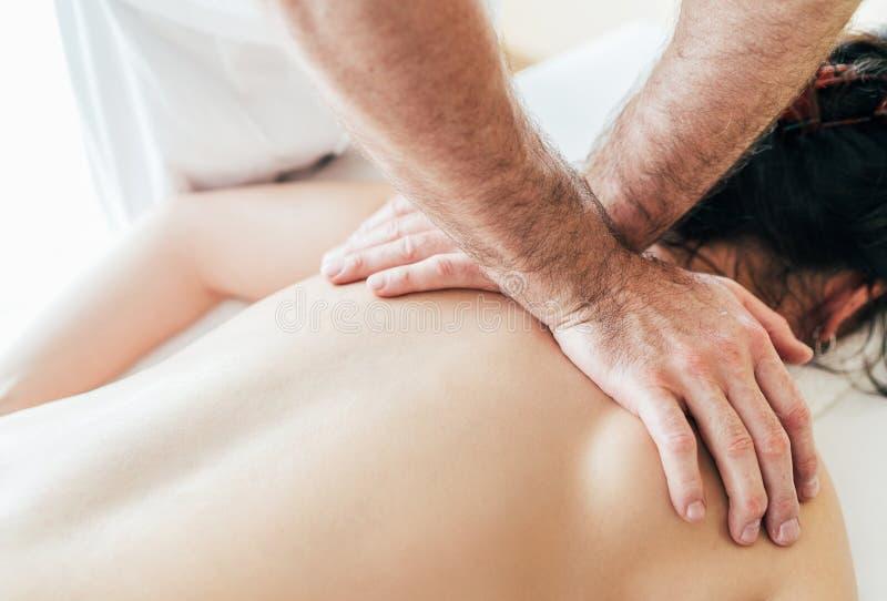 Mani dell'uomo del massaggiatore che fanno le manipolazioni di massaggio sulla zona di area della scapola durante il giovane mass fotografia stock libera da diritti