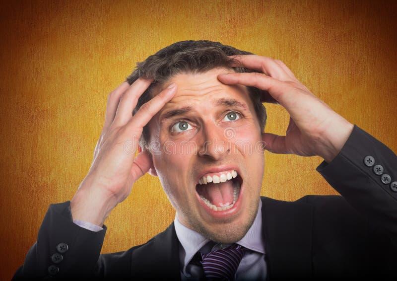 Mani dell'uomo di affari sulla testa contro la parete arancio immagini stock libere da diritti
