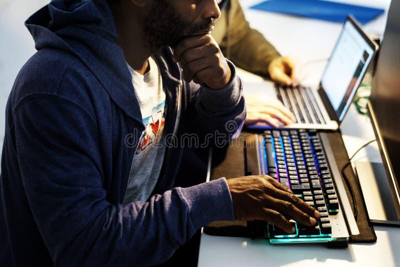 Mani dell'uomo di origine africana che lavorano alla tastiera di computer fotografie stock libere da diritti