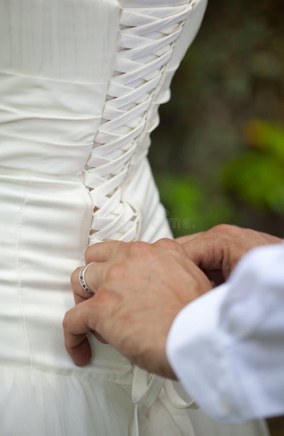Mani dell'uomo o dello sposo che merletta vestito di seta bianco della sua sposa fotografia stock libera da diritti