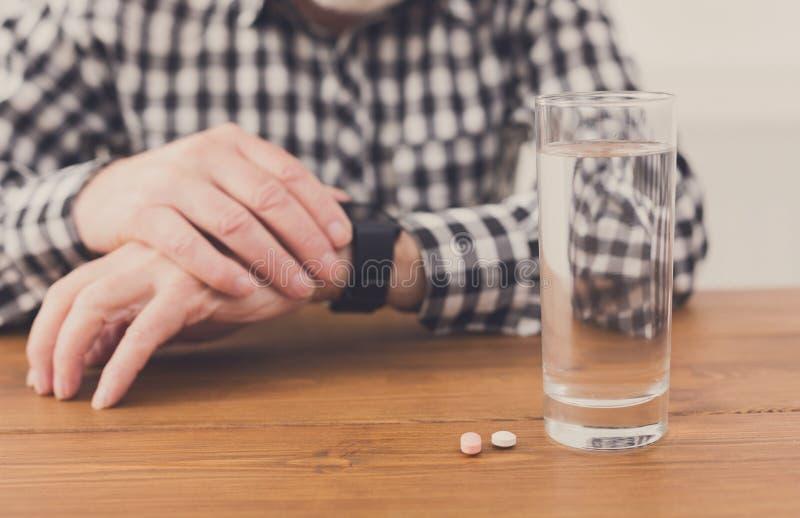 Mani dell'uomo senior con bicchiere d'acqua e le pillole immagine stock libera da diritti