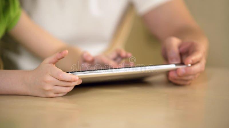 Mani della bambina che scrivono sullo schermo attivabile al tatto, sul padre e sulla figlia della compressa che usando app immagini stock libere da diritti