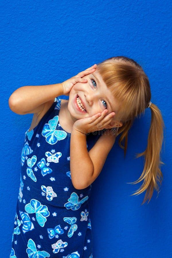Mani della bambina sulla testa del fronte inclinata immagini stock libere da diritti