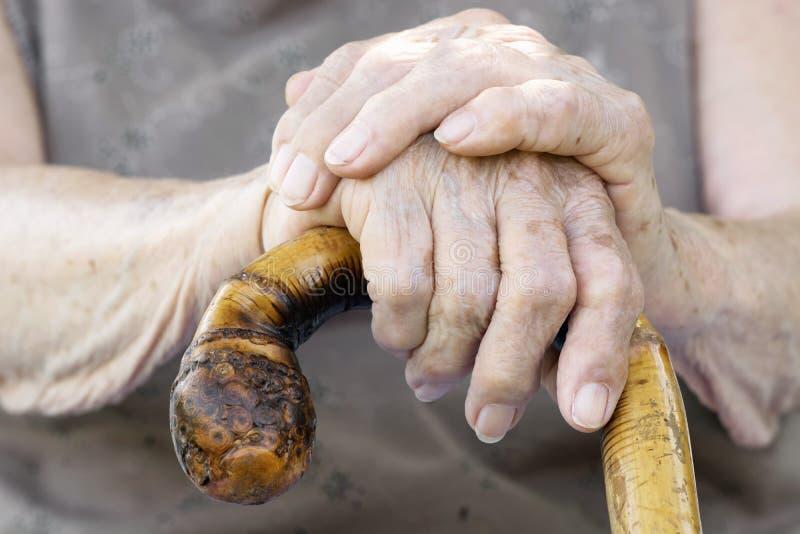 Mani della donna anziana con la canna fotografia stock