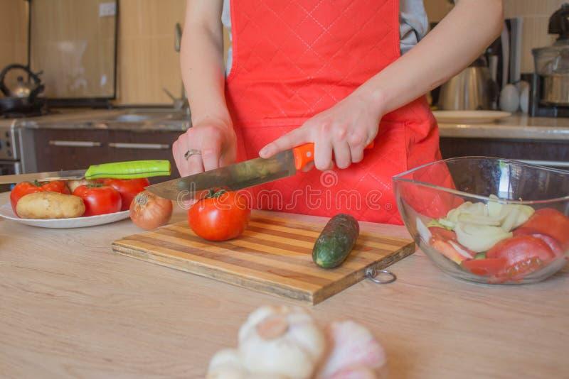 Mani della donna che cucinano pasto sano nella cucina, dietro gli ortaggi freschi Immagine potata delle verdure di taglio della r immagini stock libere da diritti