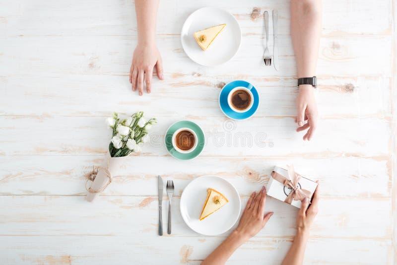 Mani della donna che danno presenti all'uomo sulla tavola di legno immagini stock libere da diritti