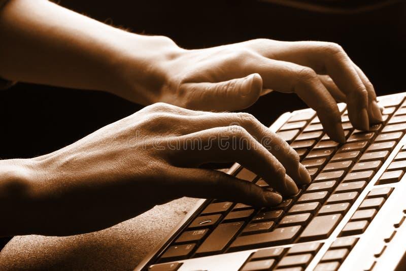 Mani della donna che digitano su un computer portatile fotografia stock libera da diritti
