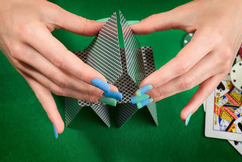 Mani della donna che montano castello di carte Contro il backgr del feltro di verde immagini stock libere da diritti