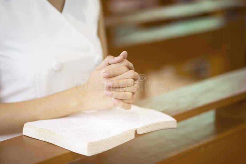 Mani della donna che pregano su una bibbia santa in chiesa per il concetto di fede, la spiritualità e la religione cristiana fotografia stock libera da diritti