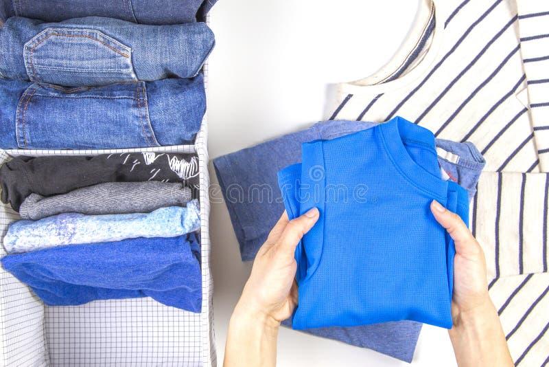 Mani della donna che riordinano la merce nel carrello dei vestiti dei bambini Stoccaggio verticale di abbigliamento, riordinante, fotografia stock