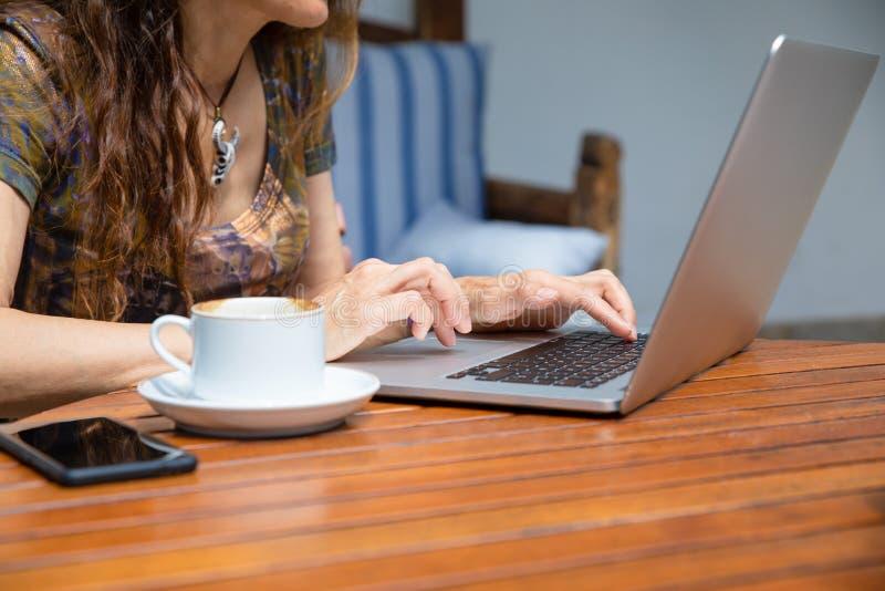 Mani della donna che scrivono sul computer portatile del pc della tastiera con la tazza di caffè su tabl immagini stock libere da diritti