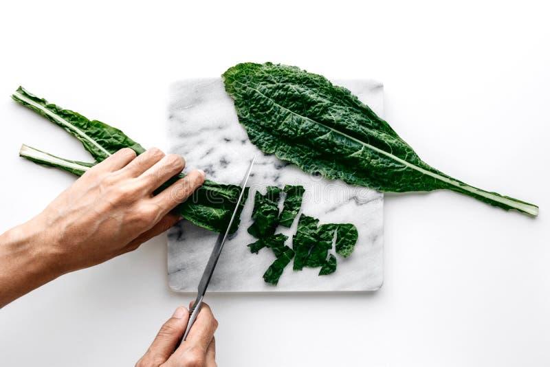 Mani della donna che tagliano le foglie verdi organiche del cavolo su un bordo di marmo sopra un fondo bianco della tavola fotografia stock