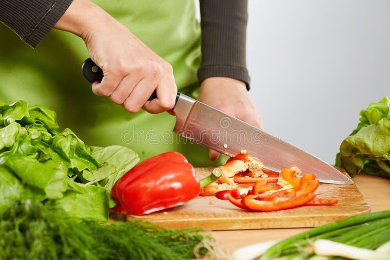 Mani della donna che tagliano le verdure a pezzi fotografia stock libera da diritti