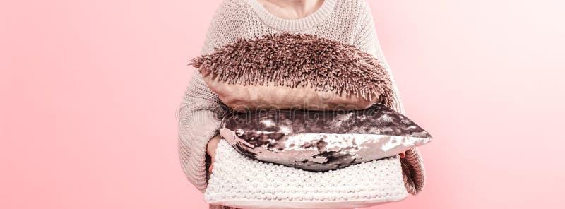 Mani della donna che tengono i tre cuscini moderni per il sofà, fondo rosa della parete nella tendenza, concetto domestico accogl fotografia stock libera da diritti