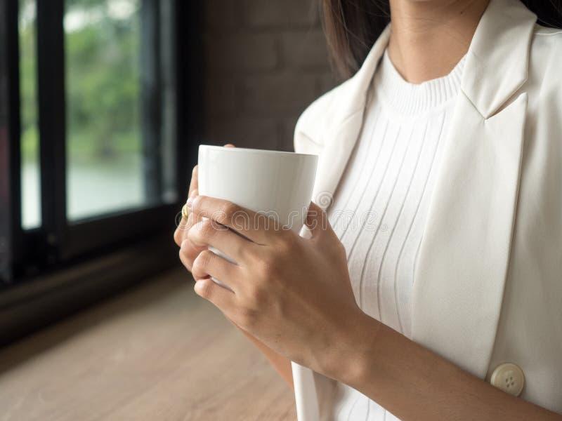 Mani della donna che tengono tazza della bevanda calda immagini stock libere da diritti
