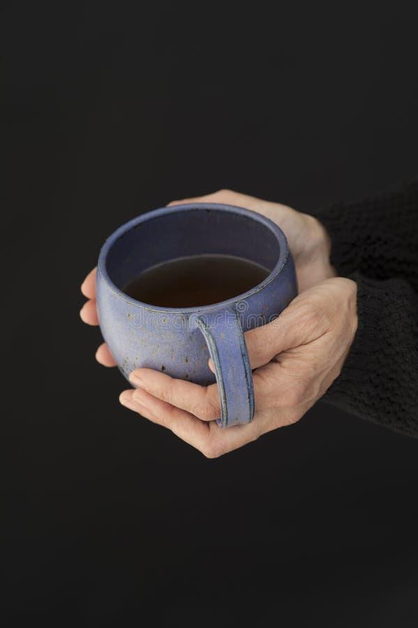 Mani della donna che tengono una grande tazza di tè fotografie stock libere da diritti