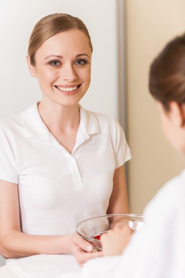 Mani della donna in ciotola di vetro con acqua sull'asciugamano bianco immagine stock