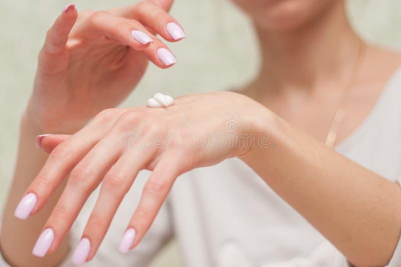 Mani della donna con crema immagine stock libera da diritti