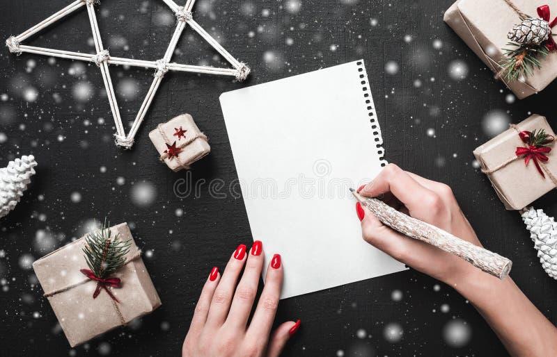 Mani della donna con i chiodi rossi che scrivono lettera con la penna d'argento Priorità bassa di natale immagini stock libere da diritti
