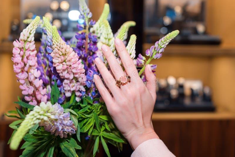 Mani della donna con il manicure e gli anelli di lusso dei gioielli Chiuda su della mano femminile sui fiori che mostrano i gioie immagine stock