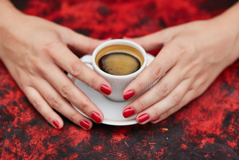 Mani della donna con il manicure e la tazza rossi di caffè fresco immagini stock