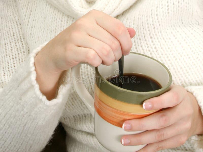 Mani della donna con la tazza di caffè e del cucchiaio immagini stock