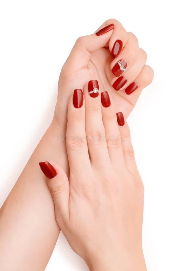 Mani della donna con smalto rosso isolato con il percorso di ritaglio fotografia stock libera da diritti