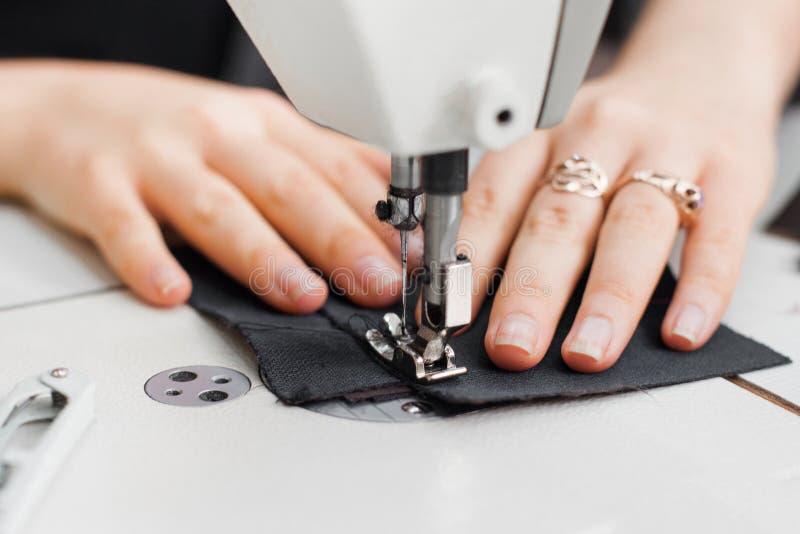 Mani della donna con tessuto alla macchina per cucire fotografie stock