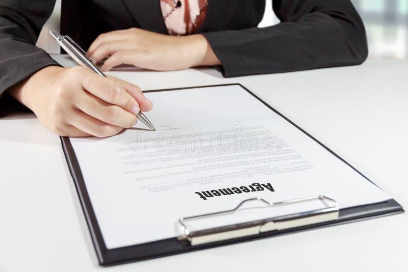 Mani della donna di affari che firmano il documento di accordo con la penna fotografia stock
