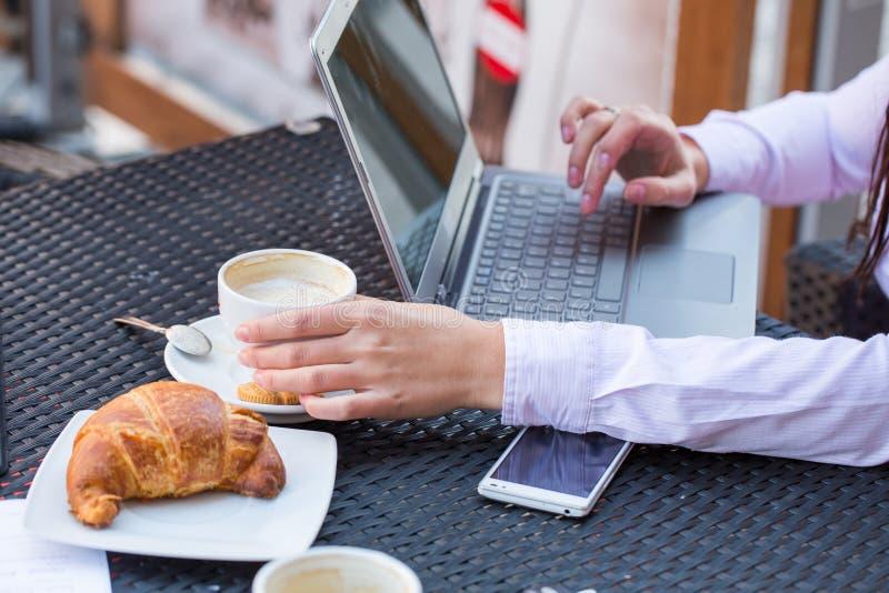 Mani della donna di affari con il computer portatile ed il telefono cellulare durante la prima colazione. fotografia stock