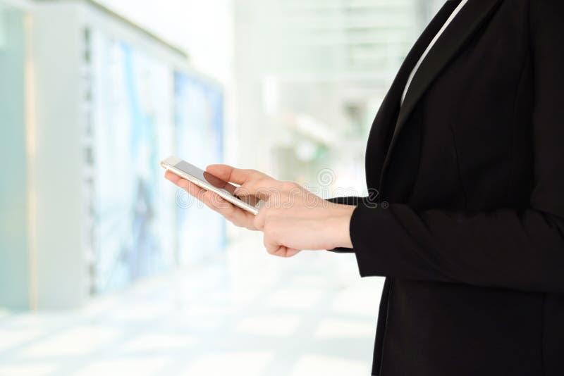 Mani della donna di affari facendo uso dello Smart Phone sopra il backgrou dell'ufficio della sfuocatura fotografie stock libere da diritti
