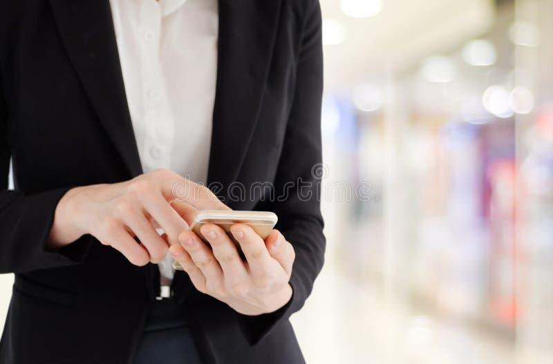 Mani della donna di affari facendo uso dello Smart Phone sopra il backgroun dell'ufficio della sfuocatura immagini stock libere da diritti