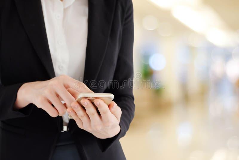 Mani della donna di affari facendo uso dello Smart Phone sopra l'ufficio della sfuocatura con bok immagini stock