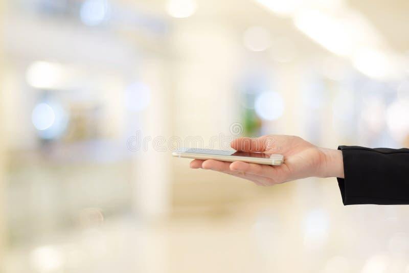Mani della donna di affari facendo uso dello Smart Phone sopra l'ufficio della sfuocatura con boke fotografia stock libera da diritti
