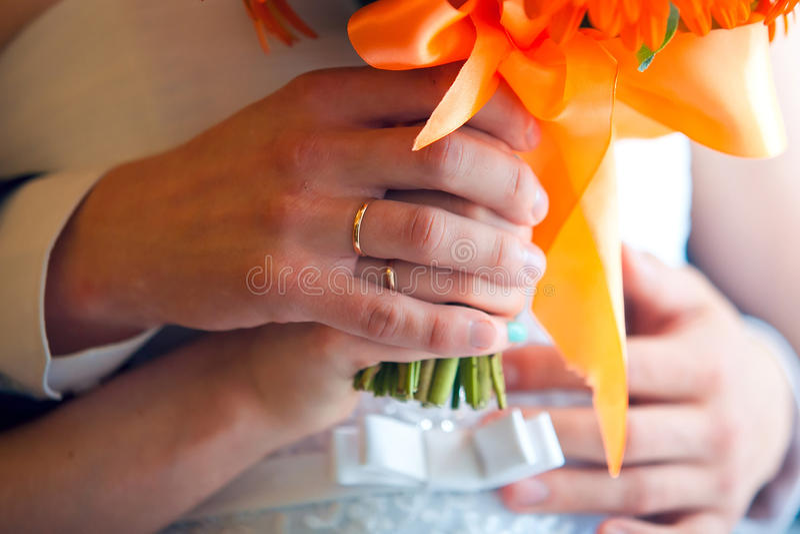 Mani della donna e dell'uomo con le fedi nuziali ed il mazzo di nozze dei fiori Sposa e sposo che si tengono per mano con le nozz immagini stock libere da diritti