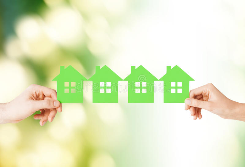 Mani della donna e dell'uomo con molte case del Libro Verde immagini stock libere da diritti