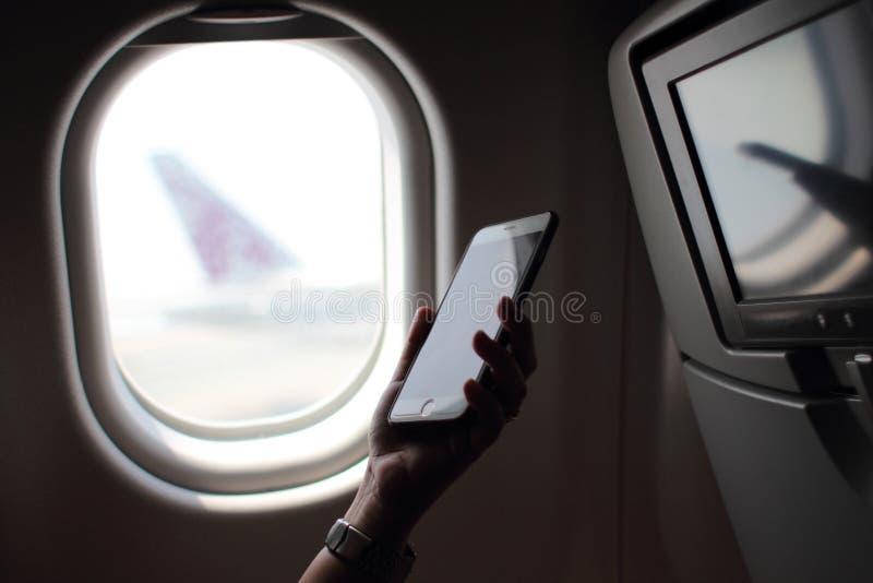 Mani della donna facendo uso dello Smart Phone sull'aereo facendo uso di Internet n fotografia stock libera da diritti